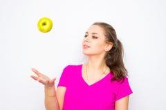 Zdrowa młoda kobieta jest ubranym w różowej koszula rzuca up zielonego jabłka obraz stock