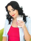 Zdrowa młoda kobieta ono Uśmiecha się Trzymający Up Świeżego Wielkiego szkło mleko Fotografia Stock