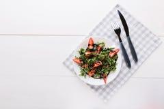Zdrowa organicznie diety sałatka z arugula, truskawkami i sezamem w bielu talerzu na popielatej pielusze na białym drewnianym tle obrazy stock