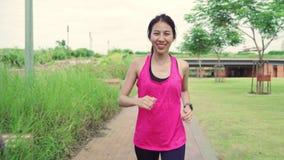 Zdrowa piękna młoda Azjatycka biegacz kobieta odziewa biegać i jogging na ulicie w miastowym miasto parku w sportach zdjęcie wideo