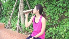 Zdrowa piękna młoda Azjatycka biegacz kobiety woda pitna ponieważ odczucie męczył po tym jak biegający na ulicie w miastowym mias zbiory wideo