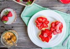 Zdrowa przekąska mała próżnuje z masłem orzechowym i świeżym strawberr Fotografia Royalty Free