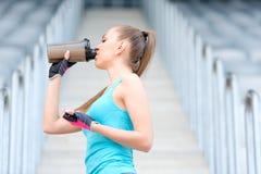 Zdrowa sprawności fizycznej dziewczyna pije proteinowego potrząśnięcie Kobieta pije sporta odżywiania napój podczas gdy pracujący Zdjęcie Royalty Free
