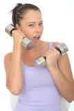 Zdrowa Szalona Dysponowana młoda kobieta Używa Niemego Dzwonkowego ciężar jako telefon komórkowy Obrazy Stock
