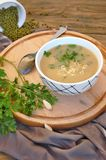 Zdrowa weganin polewka od Mung fasoli, kolenderów, czosnku i cebuli w pucharze na drewnianym tle, Obraz Royalty Free