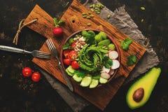 Zdrowa weganin sałatka z świeżym avocado, rzodkiew, pomidor, ogórek, seler, ziarna na tnącej desce Odgórny widok, kopia zdjęcie royalty free
