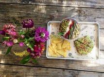 Zdrowa weganinu łasowania avocado grzanka szczerbi się kwiaty obrazy stock