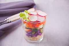 Zdrowa ?wie?a sa?atka w glassful z czerwon? kapust?, pomidorem, quinoa, zielon? sa?atk? i rzodkwi? na drewnianym stole, obrazy stock