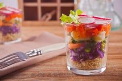 Zdrowa ?wie?a sa?atka w glassful z czerwon? kapust?, pomidorem, quinoa, zielon? sa?atk? i rzodkwi? na drewnianym stole, obraz royalty free