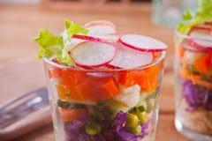 Zdrowa ?wie?a sa?atka w glassful z czerwon? kapust?, pomidorem, quinoa, zielon? sa?atk? i rzodkwi? na drewnianym stole, zdjęcie stock