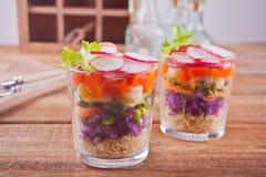 Zdrowa ?wie?a sa?atka w glassful z czerwon? kapust?, pomidorem, quinoa, zielon? sa?atk? i rzodkwi? na drewnianym stole, obraz stock