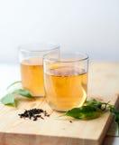 Zdrowa zielonej herbaty filiżanka z herbacianymi liśćmi Zdjęcia Royalty Free