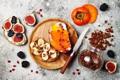 Zdrowe śniadanie grzanki z masłem orzechowym, banan, czekoladowy granola, kremowy ser, figi, czernica, persimmon, granatowiec fotografia royalty free