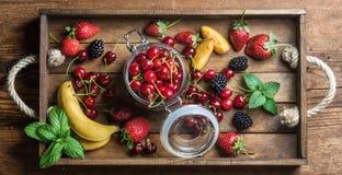 Zdrowego lata owocowa rozmaitość Słodkie wiśnie, truskawki, czernicy, brzoskwinie, banany i nowi liście, Fotografia Stock