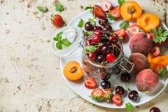 Zdrowego lata owocowa rozmaitość Słodkie wiśnie, truskawki, czernicy, brzoskwinie, banany i nowi liście na błękicie, Fotografia Stock
