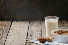 Zdrowego organicznie soi mleka nabiału bezpłatna alternatywa w filiżance i pucharze z soją na ciemnym drewnianym tle Weganin dojn fotografia royalty free