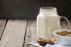 Zdrowego organicznie soi mleka nabiału bezpłatna alternatywa w słoju i pucharze z soją na ciemnym drewnianym tle Weganin dojna la fotografia royalty free