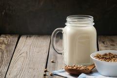 Zdrowego organicznie soi mleka nabiału bezpłatna alternatywa w słoju i pucharze z soją na ciemnym drewnianym tle Weganin dojna la zdjęcie royalty free