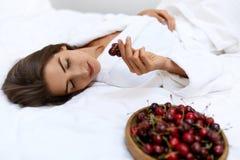 Zdrowej diety jedzenie Dla kobiet zdrowie Dziewczyny łasowania owoc Na łóżku Obrazy Stock
