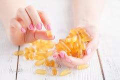 Zdrowej diety odżywianie Piękna Uśmiechnięta młoda kobieta Trzyma Rybiego oleju pigułkę W ręce Zbliżenie Bierze kapsułę Z dorszem obrazy royalty free