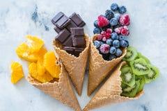 Zdrowej diety pojęcie owoc i zamarznięte jagody w lodów rożkach na nieociosanym tle - Obraz Royalty Free