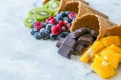 Zdrowej diety pojęcie owoc i zamarznięte jagody w lodów rożkach na nieociosanym tle - Obraz Stock