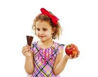Mała dziewczynka z jabłkiem i czekoladą Zdjęcie Stock
