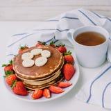 Zdrowi śniadaniowi bliny z truskawkami, banany, filiżanka czarna herbata na białym tle z białym ręcznikiem Zdjęcie Stock