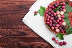 Zdrowi, świezi, dojrzali stubarwni agresty z zielonymi liśćmi w jasnobrązowym koszu na drewnianym stole, Zdjęcie Stock