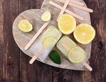 Zdrowi cytryn popsicles z świeżymi wapno plasterkami na drewnianym backgro Zdjęcie Royalty Free