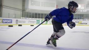 Zdrowi dzieci w ochronnym hełmie z hokejowym kijem na łyżwie uczą się bawić się hokeja na lodowym lodowisku zbiory