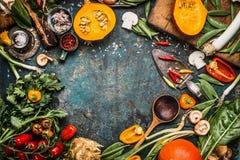 Zdrowi i organicznie żniwo składniki i warzywa: bania, zielenie, pomidory, kale, leek, chard, seler na nieociosanym kuchennego st zdjęcia stock