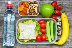 Zdrowi lunchów pudełka z kanapką, jajka, świezi warzywa, butelka woda, dokrętki i owoc, Obrazy Stock
