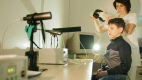Zdrowie dzieci ` s diagnostyk okulistyka szpital - optometrist stawia dalej oka wyposażenie dla nastolatek chłopiec pacjenta - zdjęcie wideo