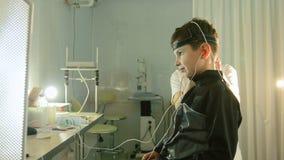 Zdrowie dzieci ` s diagnostyk okulistyki klinika - optometrist kobieta stawia dalej oka wyposażenie dla chłopiec pacjenta - zbiory