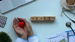 Zdrowie formułują robią drewniani sześciany na stole, doktorski mienie zabawki serce, dawca zbiory wideo