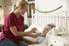 Zdrowie gość Daje Starszemu kobiety lekarstwu W łóżku W Domu Zdjęcie Stock