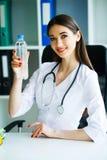 Zdrowie i piękno Dietetyczka Trzyma butelkę woda w rękach zdrowe jeść Lekarka z Szczęśliwym uśmiechem zdjęcia stock