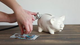 Zdrowie koszty pojęcie, pieniądze i prosiątko bank na biurku z stetoscope, zbiory