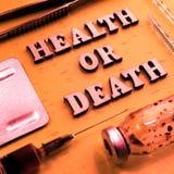 Zdrowie lub ?mierci poj?cie Inskrypcja drewniani listy Tonowa? w rocznika stylu Możny lek, strzykawka, butelka lekarstwo zdjęcia stock