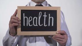 Zdrowie pisać na blackboard w lekarek rękach, opieki zdrowotnej reformy prezentacja zbiory