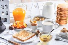 Zdrowy śniadaniowy łasowania pojęcie, różnorodny ranku jedzenie - bliny, gotujący się jajko, grzanka, oatmeal, granola, owoc, kaw fotografia royalty free