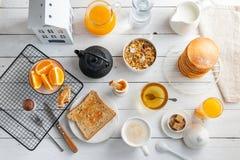 Zdrowy śniadaniowy łasowania pojęcie, różnorodny ranku jedzenie - bliny, gotujący się jajko, grzanka, oatmeal, granola, owoc obraz royalty free