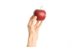 Zdrowy łasowania i diety temat: ludzka ręka trzyma czerwonego jabłka odizolowywający na białym tle w studiu, osoba widok Zdjęcia Stock