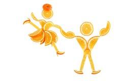 Zdrowy łasowanie. Śmieszna mała para robić pomarańczowi plasterki. Zdjęcie Stock