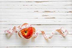 Zdrowy łasowanie i dieting pojęcie Jabłczana i pomiarowa taśma na ośniedziałym białym drewnianym tle Odgórny widok z kopii przest obraz stock
