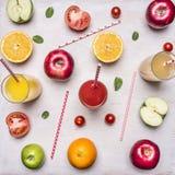 Zdrowy łasowanie, pokrojeni jabłka, pomarańcze, pomidory, składniki dla robić świeżemu sokowi, rolki, filiżanki tła drewniany nie obraz royalty free