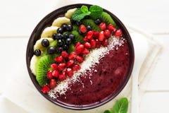 Zdrowy śniadanie: świeży smoothie z kiwi, bananem, garnet ziarnami, czarną jagodą i koksem, dekorował nowych liście Fotografia Stock
