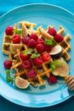 Zdrowy śniadanie: Belgijscy gofry z malinkami, miodem i figami, dekorowali nowych liście na turkusowej pielusze fotografia stock