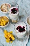 Zdrowy śniadanie: domowej roboty granola, banan, świeże jagody, jogurt w szklanych filiżankach na lekkim tekstylnym tle Pojęcie h obrazy royalty free